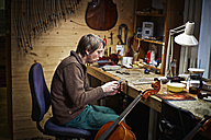 Violin maker in his workshop filing a cello mechanism - DIKF000093
