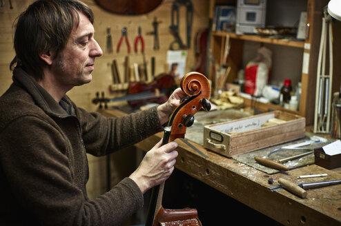 Violin maker in his workshop adjusting a cello mechanism - DIKF000105