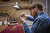 Violin maker in his workshop examining neck of an instrument - DIKF000109