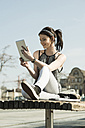 Young woman with tablet computer sitting on a bench - UUF000163