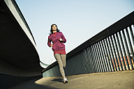 Young female jogger on the move on a bridge - UUF000102