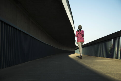 Young female jogger on the move on a bridge - UUF000104