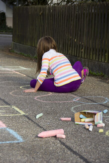 Girl drawing with coloured crayon on asphalt - YFF000084