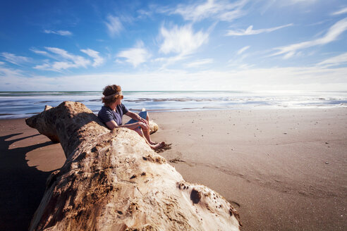 New Zealand, Wanganui beach, Young man sitting on beach - WV000562