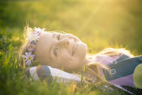 Portrait of smiling little girl lying on meadow wearing flowers - SARF000429