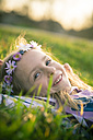 Portrait of smiling little girl lying on meadow wearing flowers - SARF000431