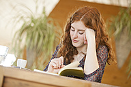 Young woman with note-book writing in cafe - DISF000718