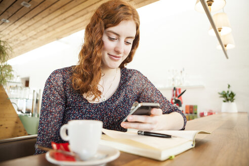 Portrait of young woman with smartphone reading SMS - DISF000721