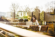 Young woman using notebook in cafe, view from outside - DISF000707