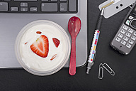 Workplace with strawberry yoghurt on laptop - CSTF000215