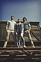 Three friends with sunglasses standing in front of old freight car - HOHF000664