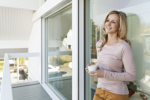 Woman with a cup of coffee leaning at glass front of her house - MFF000962