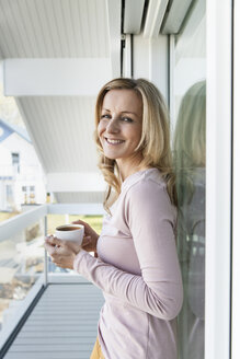 Smiling woman standing on balcony of her house with a cup of coffee - MFF000965