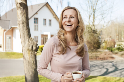 Laughing woman with cup of coffee standing in front of residential area - MFF000969