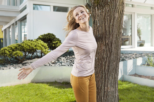 Smiling woman dancing around a tree in front of residential house - MFF000974