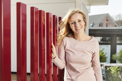 Smiling woman standing by red fence of residential house - MFF000979