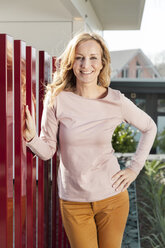 Smiling woman standing by red fence of residential house - MFF000980