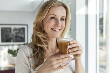 Portrait of happy woman with beverage  in her bright modern home - MFF000991