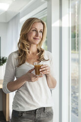 Portrait of happy woman with beverage  standing in her bright modern home - MFF000958
