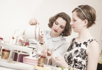 Two young women on a retro style tea party - DISF000738