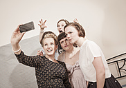 Young women in vintage dresses taking a selfie - DISF000755