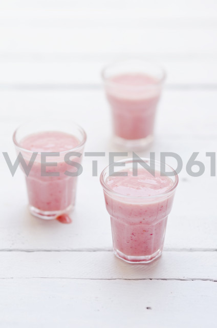 Three glasses of banana strawberry buttermilk shake on white wooden table - CZF000144