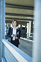 Portrait of business woman with smartphone and tablet computer on parking level - UUF000108