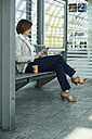 Business woman with smartphone and tablet computer waiting on platform - UUF000130