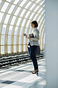 Business woman with smartphone and tablet computer waiting on platform - UUF000124