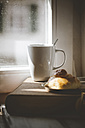Mug of coffee with brioche on old book - SBDF000766