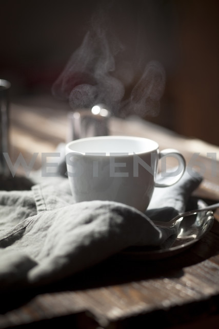 Cup of steaming tea on silver plate and wooden table - SBDF000763 - Susan Brooks-Dammann/Westend61