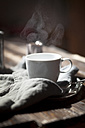 Cup of steaming tea on silver plate and wooden table - SBDF000763