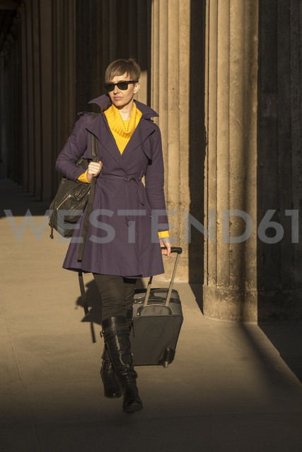 Germany, Berlin, female tourist on the move with rolling suitcase - FBF000317