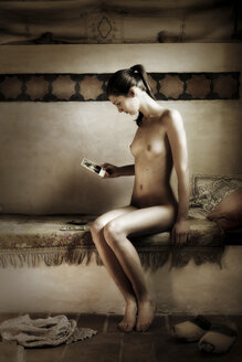Nude woman looking at photography - CvK000039