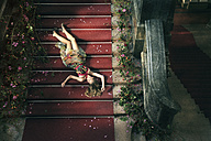 Woman lying on stairs with rose petals - CvK000090
