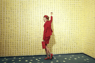 Woman standing at wall covered with adhesive notes - CvK000102
