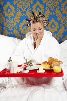 Woman with curlers and white bathrobe having breakfast in bed - CSBF000004