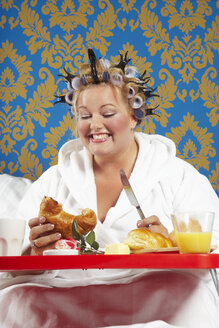 Woman with curlers and white bathrobe having breakfast in bed - CSBF000007