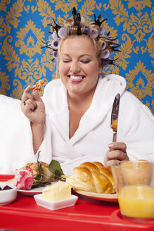 Portrait of woman with curlers and white bathrobe having breakfast in bed - CSBF000010