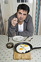 Portrait of man with bad habit sitting at breakfast table - CSBF000016