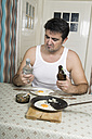 Portrait of man with bad habit sitting at breakfast table - CSBF000019