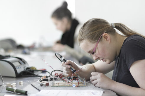 Two young women working on optical sensor in an electronic workshop - SGF000542