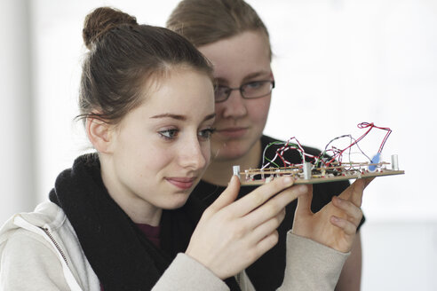 Two young women holding component an optical sensor in an electronic workshop - SGF000544
