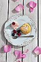 Muffin, berries and creme on plate and wooden table, elevated view - CSF021202