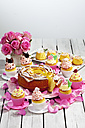 Birthday cake, cupcakes, muffins and flower vase of pink roses on wooden table - CSF021211