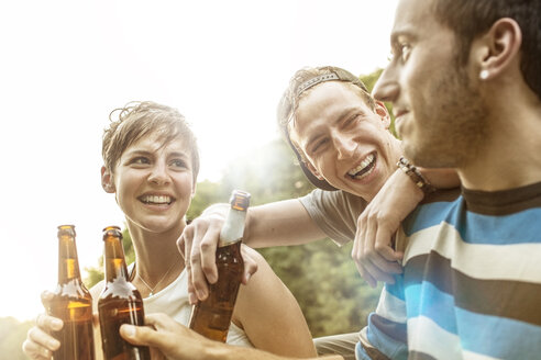 Three frinds relaxing with bottles of beer - MUMF000008