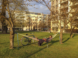 Germany, Berlin, Young woman sitting in hammock in Monbijou park, reading - FBF000319
