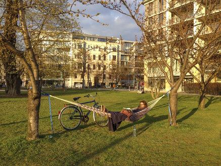Germany, Berlin, Young woman sitting in hammock in Monbijou park, reading - FBF000319