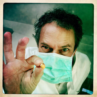 Doctor with drug in hand in an exaggerated pose, Freiburg, Germany - DRF000624