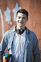 Portrait of smiling teenager with headphones and folders - UUF000188